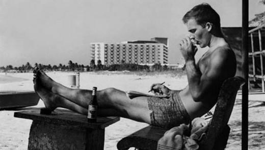 Hunter S. Thompson aan het werk in Aruba. De foto is gemaakt bij de Aruba Palm Beach Club met op de achtergrond het Aruba Caribbean Hotel. Thompson bezocht Aruba terwijl hij woonde op Puerto Rico.